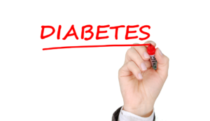 """An image of a hand underling the word """"DIABETES"""" in red marker. All Type 1 diabetics and many Type 2 diabetics depend on insulin to stay alive."""