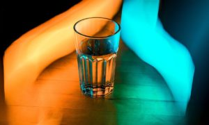 An image of a clear glass of water reflecting the light of an orange swirl of light on the left and a blue swirl of light on the right.