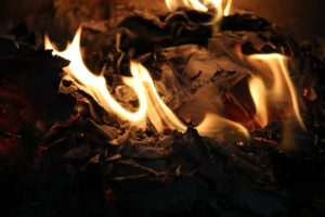 An image of crumpled paper as it burns, with flames visible around the edges.