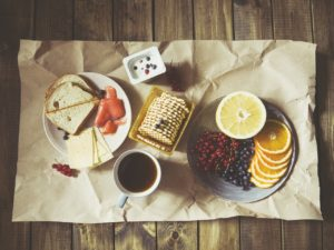 An image for your taste buds. A plate of bread and cheese with sliced salmon, a cup of yogurt with berries, a container of fancy crackers, a mug of black coffee, and a plate with red and black grapes, circular orange slices, and a half of grapefruit. It's all laid out on brown parchment paper on a table of raw wood planks.
